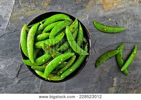 Bowl Of Healthy Roasted Snap Peas. Top View Over A Dark Slate Background.