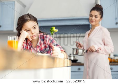 It Is Disgusting. Beautiful Unsmiling Dark-haired Little Girl Having Healthy Breakfast And Looking A