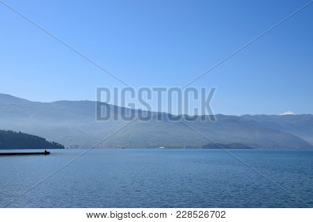 Ohrid Lake View With Fishing Man And Mountain Background, Macedonia.