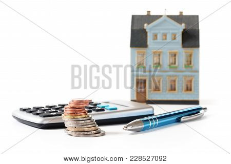 Coins, Calculator And Pen In Front Of A Blurred House Model, Calculation Of The Cost Of A Real Estat