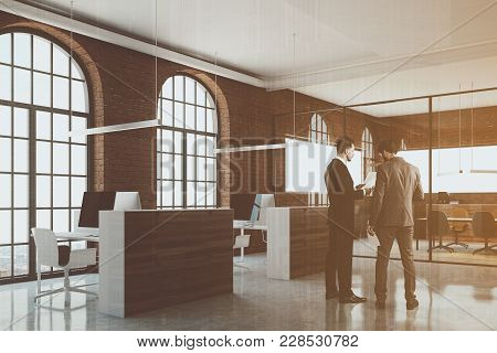 Brick Open Space Office Interior With Arch Windows, A Concrete Floor And Cubicles. A Side View. Busi