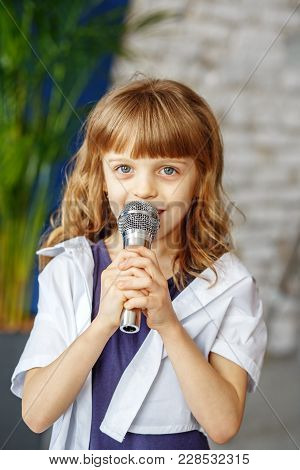 A Little Beautiful Kid Sings A Song In A Microphone. The Concept Is Childhood, Lifestyle, Music, Sin