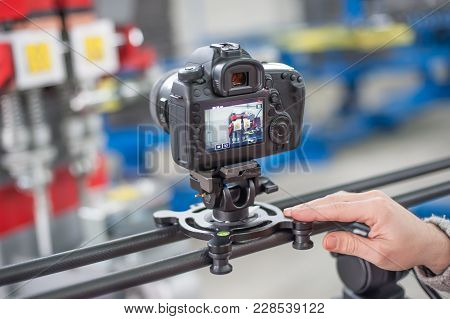 Videographer Using Camera Slider, Making Video Of Business At Factory