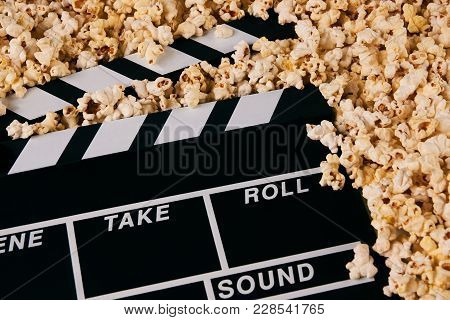 Clapper Board And Pop Corn. Black Wooden Movie Clapper With Sweet Popcorn, Close-up. Movie Time Conc