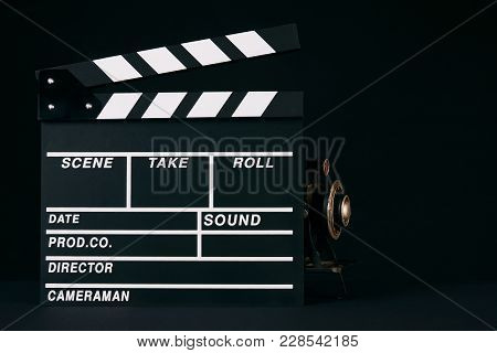 Old Movie Camera Model Behind A Clapper Board As Cinema And Movie Time Concept. Dark Background With