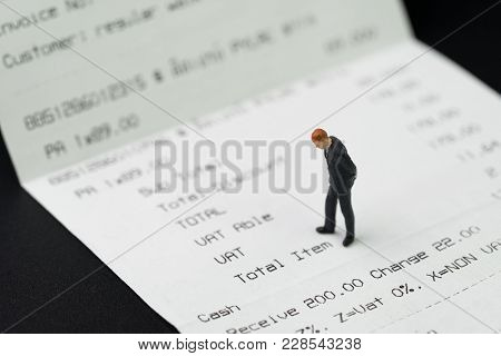 Miniature Businessman Figurine Standing On Printed Payment Invoice Or Receipt And Looking At Vat Lin