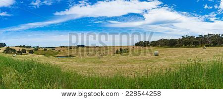 Picturesque Panorama Landscape Of Countryside Field With Straw Bales On Sunny Day