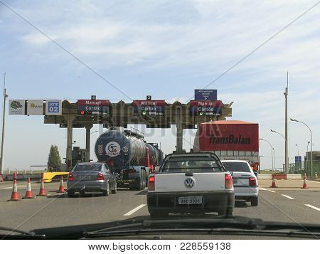 Parana, Brazil, July 29, 2003: Drivers Pays In Toll Station On The Road In Paraiso Do Norte City