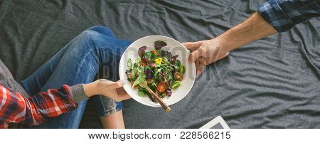 Man Brought A Salad In Bed To His Beloved Woman. Concept Of Love And Care