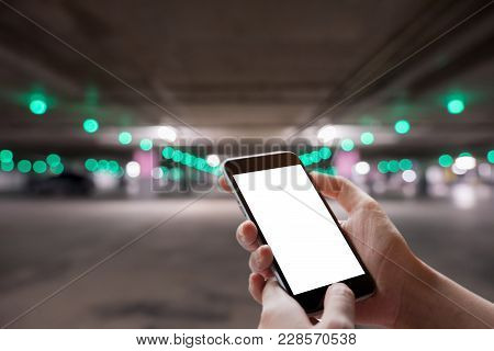 A Man Hand Holding Smart Phone Device With Car Park Bokeh Background.