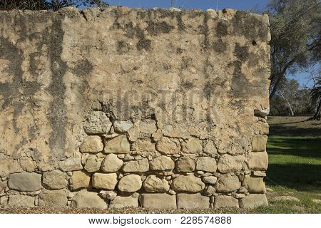 Detail Shot At Eye Level Of A Worn Sandstone Wall With Eroding Features Exposing The Stones Undernea