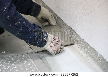 Repairs. Laying Of Floor Ceramic Tiles. Men's Hands In Gloves With  Spatula, Spread  Cement Mortar O
