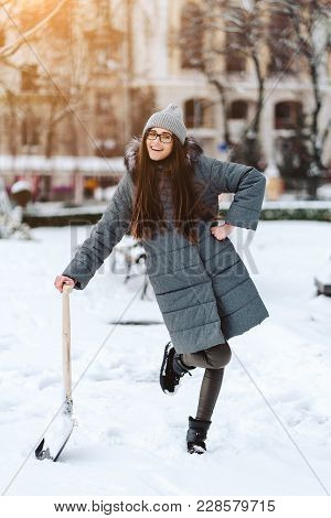 Beautiful Girl In Winter Fashion Clothes With A Shovel, Posing On Camera