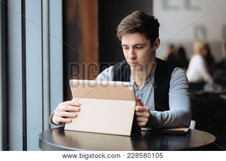 Business, Technology And People Concept - Young Man With Tablet Pc Computer At Cafe