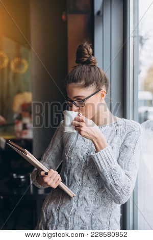 Young Girl Looking At Tablet And Smiling In Cafe With Big Window. She Has Beverage In Hand