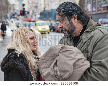 Couple Of Freezing Poor Homeless People In The Winter Cold Outdoors.