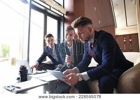 Startup Business Team On Meeting In Modern Bright Office Interior Brainstorming, Working On Laptop A