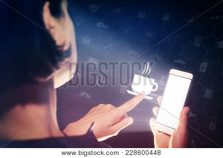 Image Of A Woman With A Smartphone In Her Hand. She Touch The Icon Cup With Hot Drink. She Lookin A