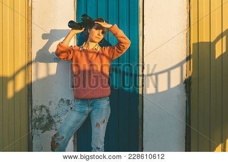Young Beautiful Girl Stands Near Colorful Wall With Binoculars In Hand And Staring Into The Distance
