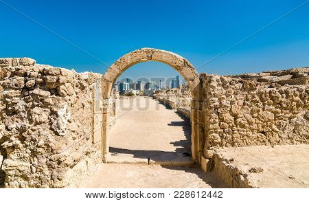 Ancient Arch At Bahrain Fort With Manama Skyline. A Unesco World Heritage Site In The Middle East
