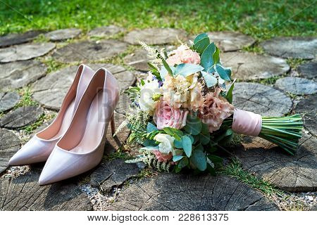 Close Up Of Beige Bride Shoes With High Heels In Front Of Wedding Bouquet In Blur On Wood Background