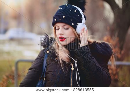 Young Sensual Blonde Caucasian Woman Wid Red Lips And Winter Cap Listening Music By Headphones Outdo
