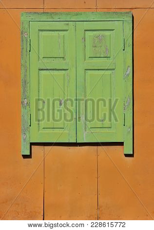 Old Sealed Wooden Window. Wooden Green Window On Orange Wall Is Closed.