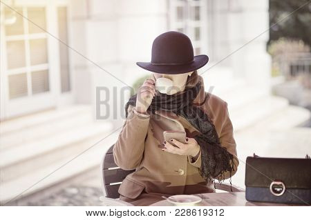 Young Classy Woman Wearing Wool Coat And Hat Sitting In Outdoors Cafe Drinking Espresso And Looking