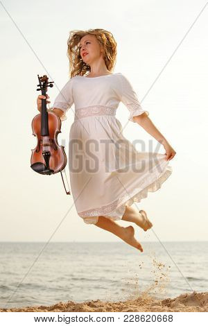 Happy Crazy Blonde Girl Music Lover On Beach Jumping With A Violin. Love Of Music Concept.