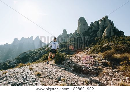 Fast And Strong, Fit Athletic Man Runs On Mountain Path Or Trail During Ultra Marathon Race, Hard Tr