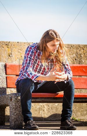 Man Long Hair Alone On Bench, Lost In Thought, Is Concerned And Stressed About Events In His Life. U