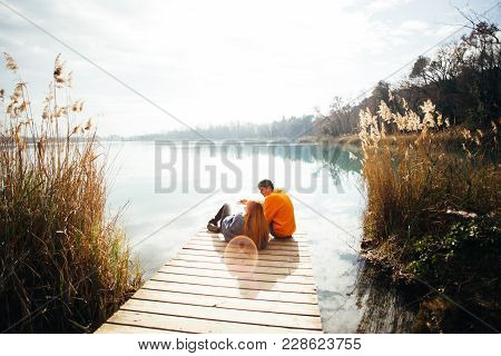 Young Hipster Couple Of Millennials, Love Birds Sit On Pier In Park Overlook Big Lake Or River Durin