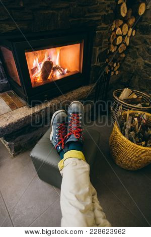 Pov Photo From Above Of Man Resting His Feet In Hard Labor Leather Winter Boots In Front Of Warm And