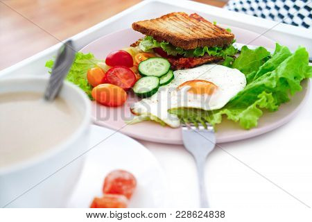 A Beautiful Breakfast On The  On The Bed Table Tray. Grilled Sandwich, Fried Eggs And Coffee. Delici