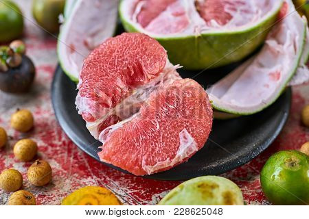 Savory Exotic Fruit On The Shabby Wooden Red Table. There Is A Sliced Pomelo On The Black Plate, Cit
