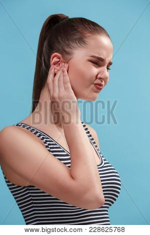 Sore Ear. Ear Ache Concept. The Sad Crying Woman With Headache Or Pain On Trendy Blue Studio Backgro