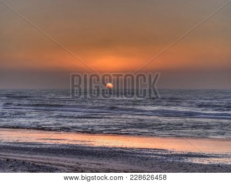 Ocean Sunset With Reflections Off The Wet Sand On A Deserted Beach Of The Orange Glow In The Sky And