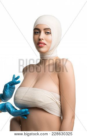 Beautiful Woman With Bandaged Face And Breasts Examined By A Plastic Surgeon Isolated Shot On White