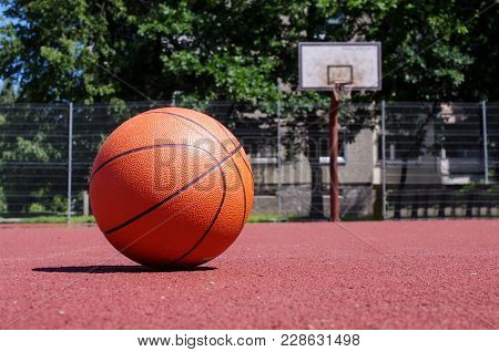 Outdoors Basketball Court With Basketball Ball During Sunny Day