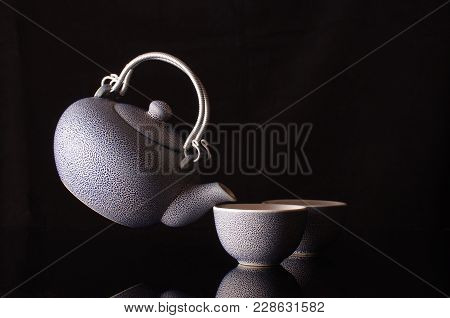 Old Style Kettle And Coffee Cups In Creative Still Life With Flying Kettle