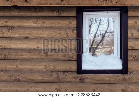 Plastic Tinted Window Covered By Snow On Wooden Wall Background.