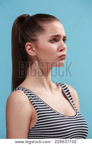 Beautiful Female Three-quarters Portrait. Isolated On Blue Studio Backgroud. The Young Emotional Sad