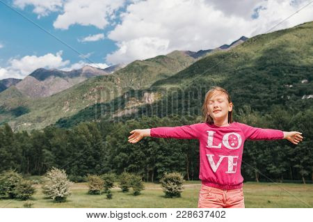 Pretty Kid Girl Resting In Mountains, Arms Wide Open, Eyes Closed, Wearing Pink Clothes. Love Sign