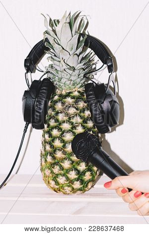 Pineapple In Earphones Hand With Microphone Stretches To Pineapple In Earphones