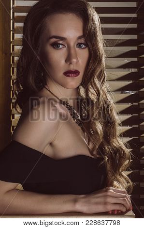 Portrait Of An Attractive Brown-haired Woman In A Black Evening Dress, A Retro Image. Studio Photo.