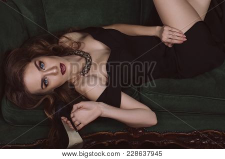 An Attractive, Stylish Young Woman In A Black Evening Dress With Open Shoulders And Vein Make-up Lie