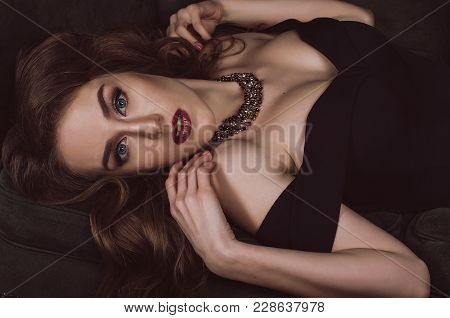 An Attractive, Stylish Young Woman In A Black Evening Dress With Open Shoulders And Evening Make-up