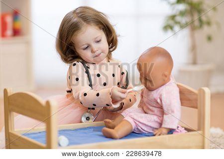 Cute Kid In Kindergarten. Kid In Nursery School. Little Girl Preschooler Playing Doctor With Doll.