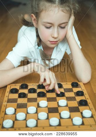 Little Cute Girl Playing Checkers Board Game.