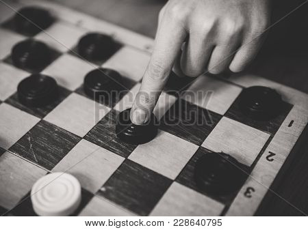 Child Playing Checkers Board Game. Black And White.